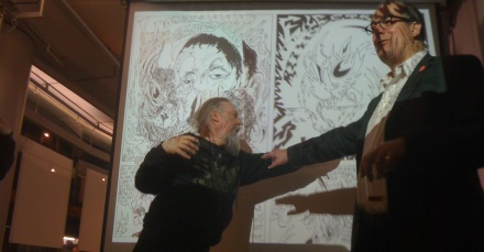 Savage Pencil and David Quantick in front of pages from their comic about Louis Wain in Dodgem Logic #7